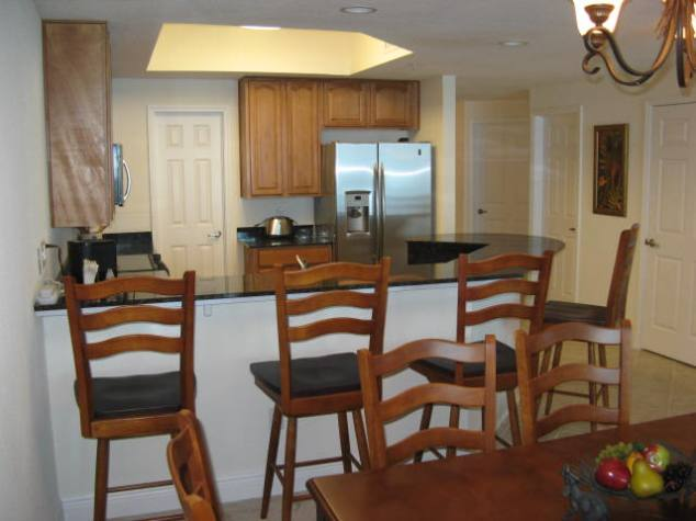 Granite breakfast bar with bar stools.  Fully stocked kitchen with stainless appliances